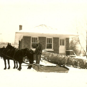 Beech log delivered to the mill on a sled.  The Jasper Veneer Mills office in the background.  This is sometime after 1929, for the office was built in 1929.
