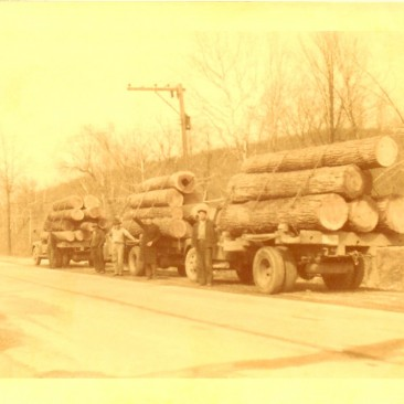 Three log trucks with nice veneer logs.  Virgil Gramelspacher in overcoat with his arm extended.  The loggers are not known.